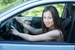 Happy young woman driving a car