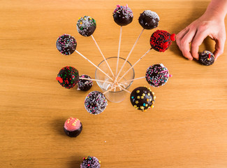 cake-pops in stick in a glass with a helping hand
