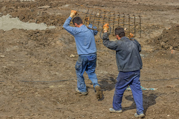 Workers carrying reinforcing rod for a concrete column