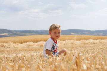 Little boy sitting on the stubble.