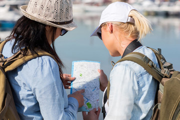 female tourists sightseeing and looking at a map