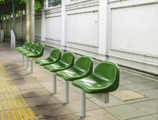 Bus station with green plastic seats in city