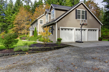 House exterior. View of three car garage with driveway and baske