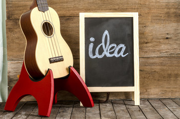 "Ukulele  and blackboard  with the word  ""idea"""