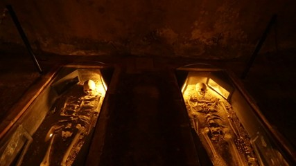 Skeletons laid down in a cave.  Dark but with yellow tones