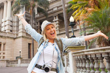 tourist arms up in front of historical building