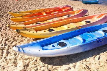 Row of colorful kayaks at sea shore