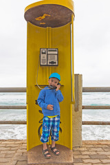 European boy  is talking on the phone, the yellow phone booth