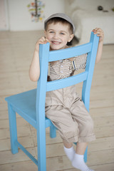little boy is smiling on a chair