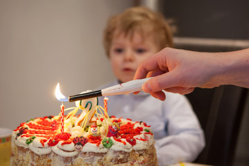Little toddler blowing candles on his 2 birthday cake