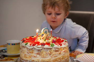 Toddler child blowing candles on his 2 birthday cake