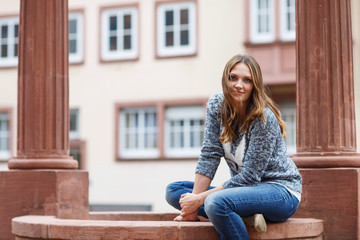 Beautiful girl sitting on fountain in german city