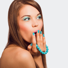 Young surprised woman holding a turquoise bracelet with bright m