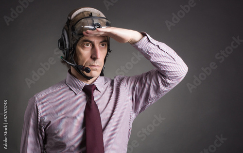 Businessman in helmet pilot looks into the distance. - 67070248