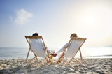 romantic couple on deckchair relaxing on the beach