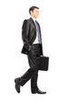 Happy business man holding a briefcase and walking