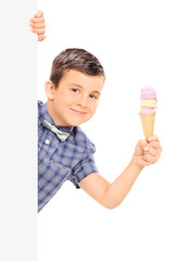 Little boy holding an ice cream behind a blank panel