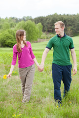 Couple in love walking on meadow