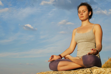 young woman practicing yoga on the stone at the sky background