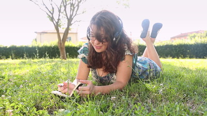 Beautiful Young Woman at Park Writing on Notepad