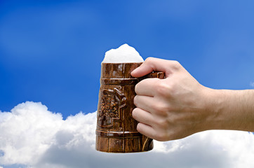 beer glass in a hand against the sky