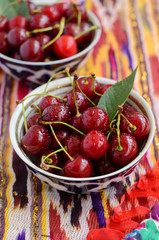 Ripe cherry in uzbek tea bowls on ethnic tablecloth