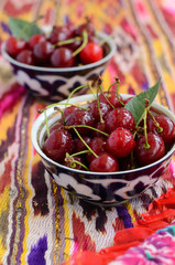 Ripe cherry in oriental bowls on bright ethnic fabric