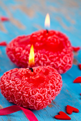 red candle, hearts and ribbons on a blue wooden surface