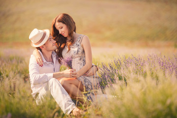 Portrait of a young couple posing in summer in the field