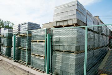 Packed cinder blocks outdoors in racks.