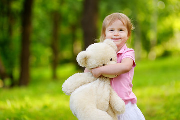 Adorable little toddler girl with a big teddy bear