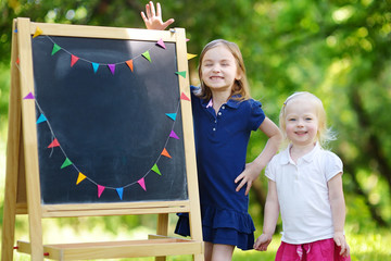 Two excited little sisters by a chalkboard