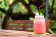 A glass of strawberry smoothie on a wooden background
