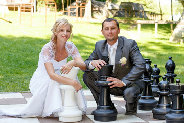 beautiful young wedding couple and outdoor chess