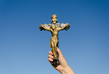 metal cross crucified christ in hand on blue sky