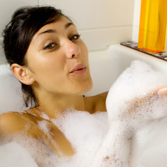 Happy woman playing with foam in bath tub