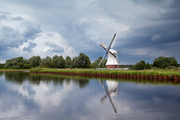 white windmill over clouded sky