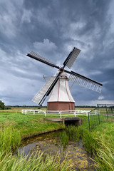 Dutch windmill over clouded sky