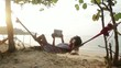 Attractive woman with digital tablet on hammock