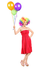 Girl with wig holding a bunch of balloons