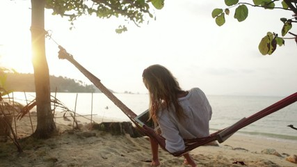 Young woman using digital tablet on hammock by the beach
