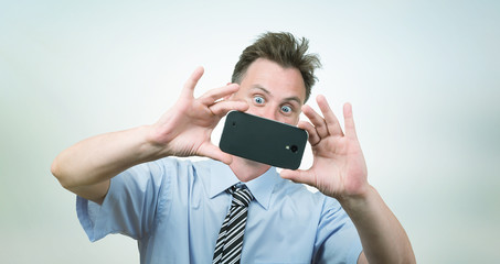 Businessman photographs smartphone