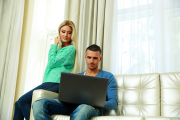 Happy couple sitting at the sofa and using laptop at home