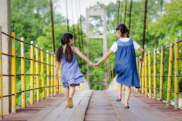 Lovely Asian girls walking together on the bridge