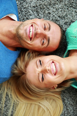 Laughing young couple lying on the carpet