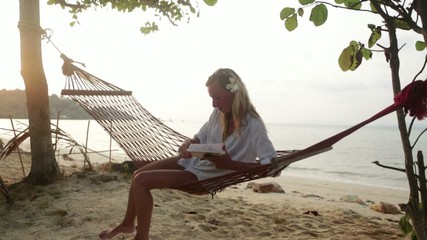 Attractive woman reading a book on hammock