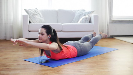 smiling woman with smartphone exercising at home