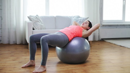 girl exercising with fitness ball at home