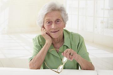 Portrait d'une femme senior tenant ses lunettes
