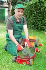 Gärtner reinigt Rasenmäher
